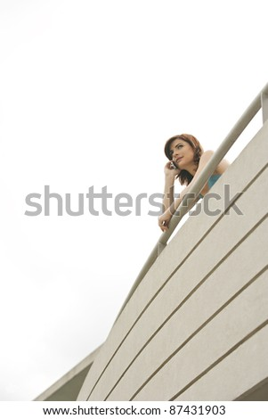 Businesswoman using a cell phone on a modern balcony.