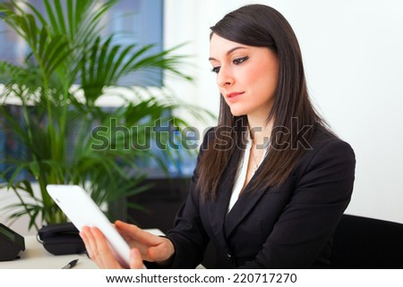 Businesswoman using a digital tablet in her office - stock photo