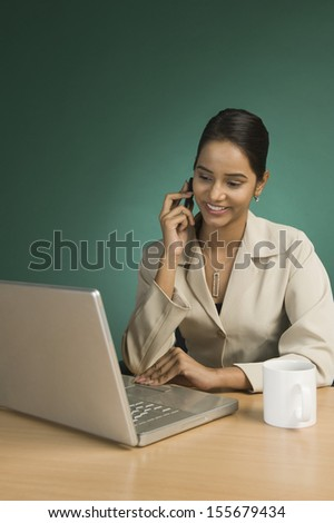 Businesswoman using a laptop and talking on a mobile phone