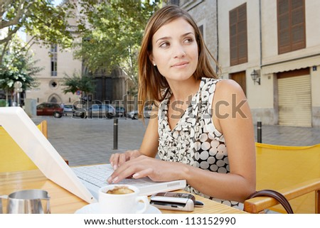 Businesswoman using a laptop computer while having a coffee in a coffee shop terrace, outdoors. - stock photo