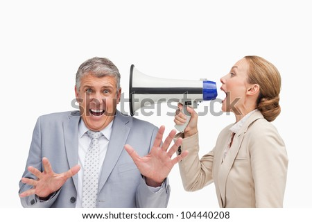 Businesswoman using a megaphone after her colleague against white background - stock photo
