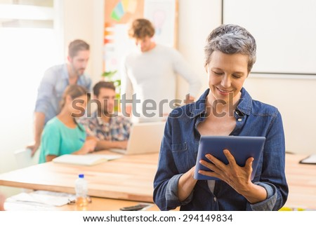 Businesswoman using a tablet with colleagues behind in office - stock photo