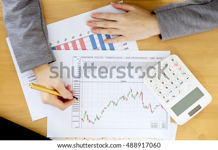 Businesswoman using calculator while analyzing graphs
