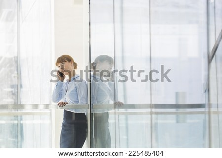 Businesswoman using cell phone in office - stock photo