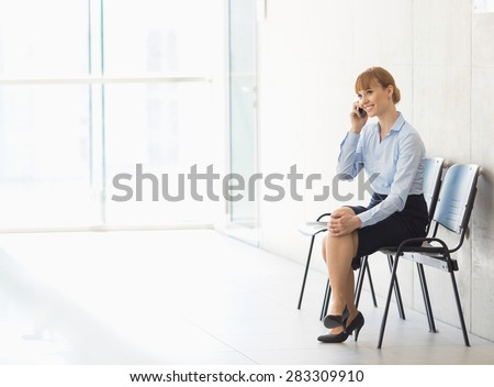 Businesswoman using cell phone while sitting on chair in office - stock photo