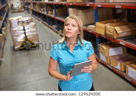 Businesswoman Using Digital Tablet In Distribution Warehouse - stock photo