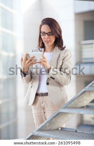 Businesswoman using digital tablet in office building - stock photo