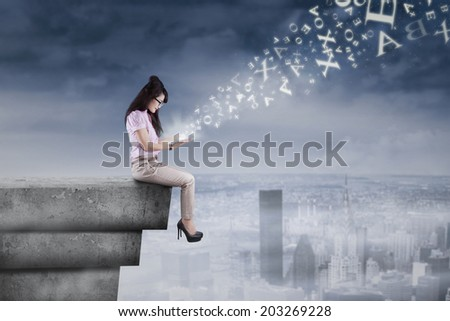Businesswoman using digital tablet on the rooftop with flying alphabet - stock photo