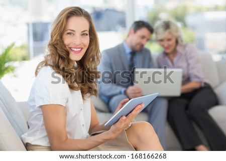 Businesswoman using digital tablet with colleagues using laptop in background at home