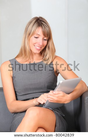 Businesswoman using electronic tablet in waiting room - stock photo