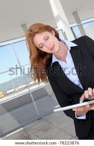 Businesswoman using electronic tablet outside