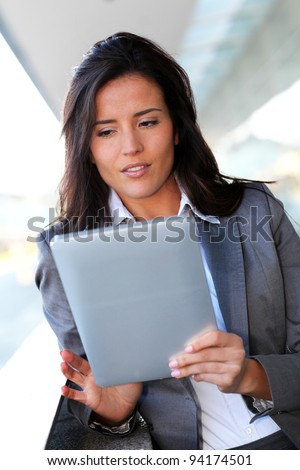 Businesswoman using electronic tablet outside the office