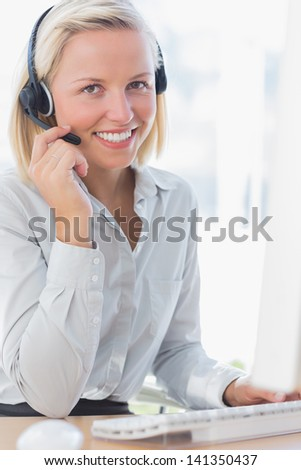 Businesswoman using headset and smiling at camera at her desk