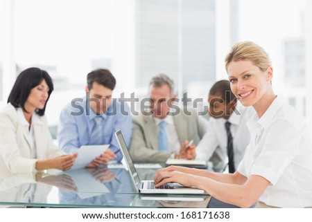 Businesswoman using her laptop during a meeting smiling at camera in the office