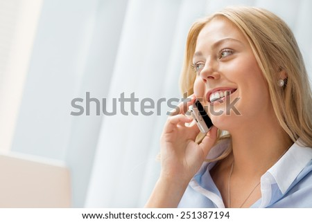 Businesswoman using her mobile in offfice - stock photo