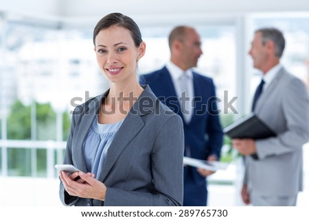 businesswoman using her phone with two colleague behind her at the office