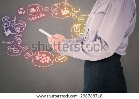 Businesswoman using her tablet against grey background - stock photo