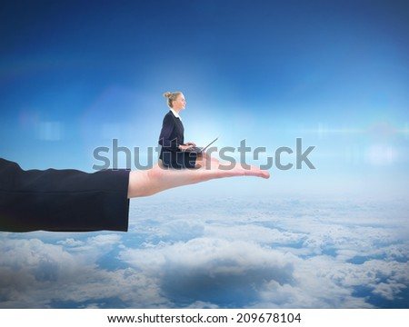 Businesswoman using laptop against blue sky over clouds at high altitude