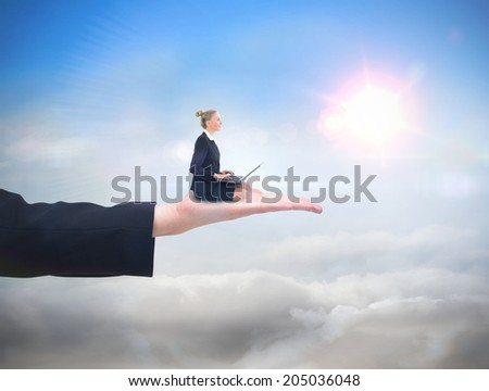 Businesswoman using laptop against blue sky with sunshine and clouds