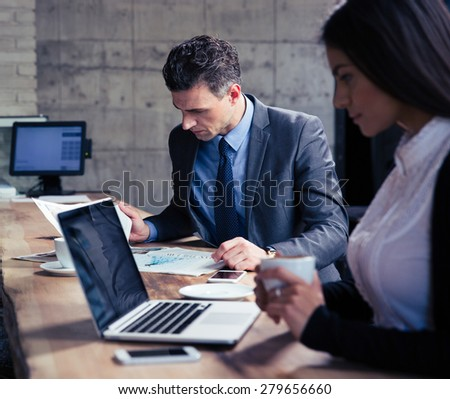 Businesswoman using laptop and businessman reading magazine in cafe - stock photo