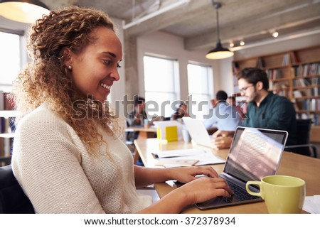 Businesswoman Using Laptop At Desk In Busy Office - stock photo