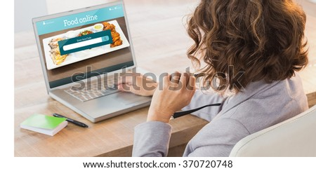 Businesswoman using laptop at desk in creative office against food app - stock photo