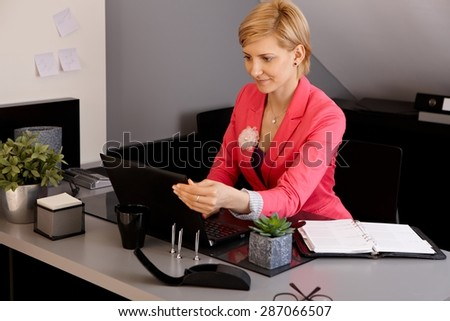 Businesswoman using laptop computer in office.