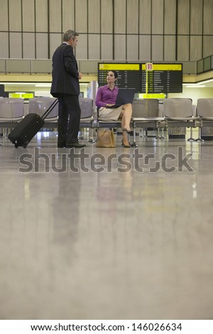 Businesswoman using laptop with businessman approaching her in airport lobby - stock photo