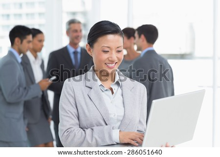 Businesswoman using laptop with colleagues behind in office - stock photo