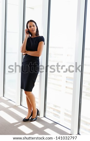 Businesswoman Using Mobile Phone In Office