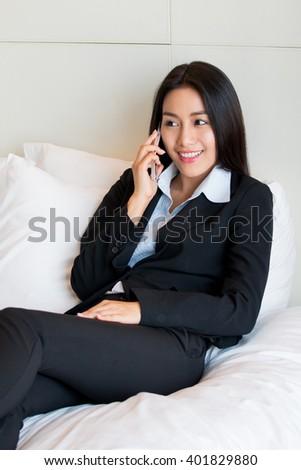 Businesswoman using mobile phone on the bed in the hotel. - stock photo
