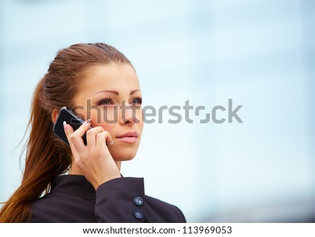 businesswoman using mobile phone outdor over building background
