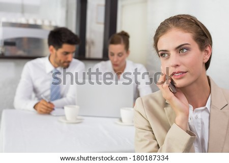 Businesswoman using mobile phone with colleagues in meeting behind at office desk
