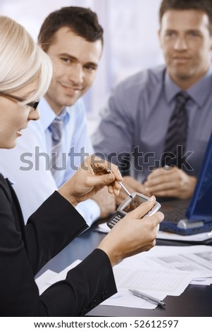 Businesswoman using PDA at office meeting, coworkers smiling in background.