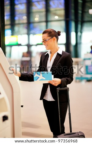businesswoman using self help check in machine in airport - stock photo