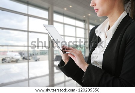 Businesswoman using tablet computer at departure lounge - stock photo