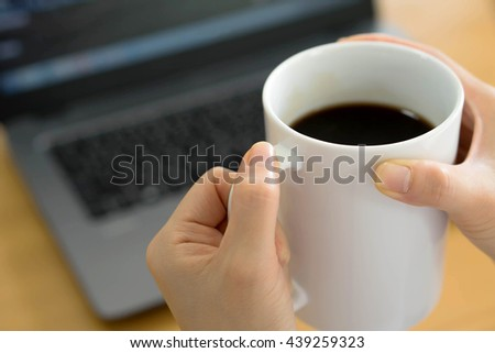 Businesswoman using tablet computer-net book and drinking coffee
