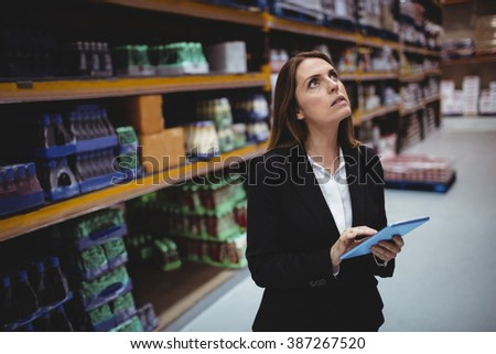 Businesswoman using tablet in warehouse - stock photo