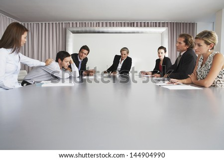 Businesswoman waking sleeping male colleague during meeting - stock photo