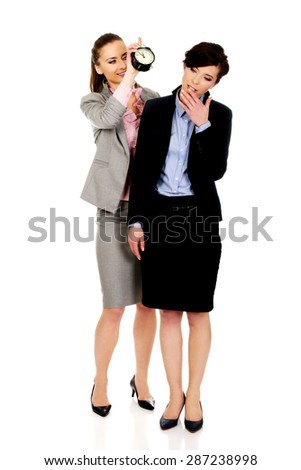 Businesswoman waking up her partner with alarm clock. - stock photo