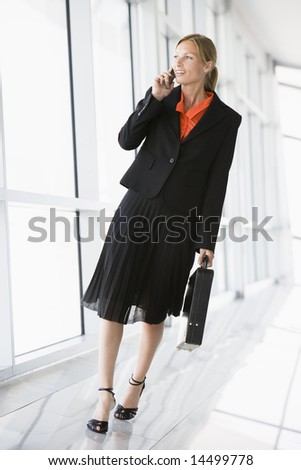 Businesswoman walking in corridor talking on cellular phone - stock photo