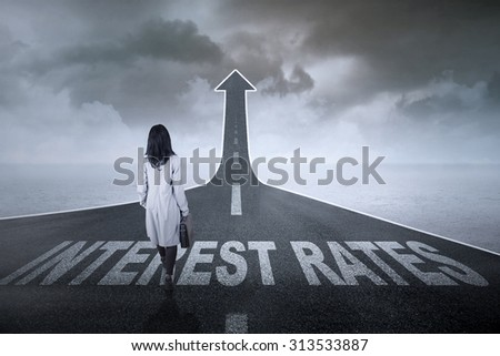 Businesswoman walking on an asphalt road turning into an ascending arrow with interest rates words on it
