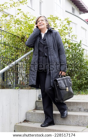 businesswoman walking on the street and talking on the phone - stock photo