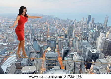 Businesswoman walking on tightrope with city in background - stock photo