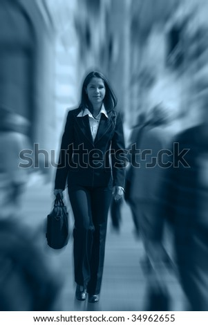 Businesswoman walking quickly in a crowded downtown.The image presents a significant spin blur effect to accentuate the dynamism of the scene. - stock photo