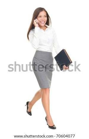 Businesswoman walking talking on mobile phone. Young stylish business woman smiling isolated on white in full body. Mixed-race chinese asian / white caucasian brunette female model.