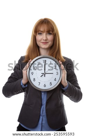 businesswoman wearing a suit holding a wall clock up to her chest