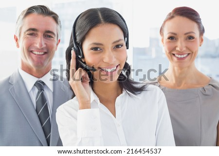 Businesswoman wearing a work headset with fellow employees
