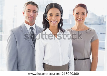 Businesswoman wearing a work headset with fellow employees - stock photo