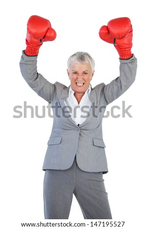 Businesswoman wearing boxing gloves and raising her arms on white background